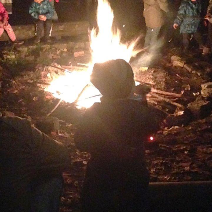 Kind steht vor dem lodernen und leuchtenden Feuer